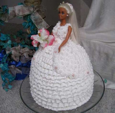 Tanned blonde Barbie doll emerges waste up from a frosting-covered white skirt