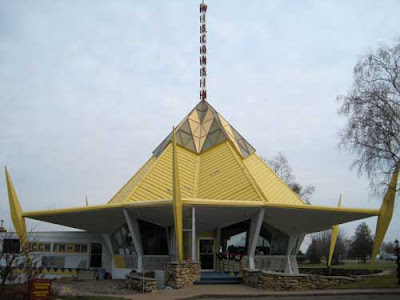 1960s circular building with yellow pointed roof and tower at top