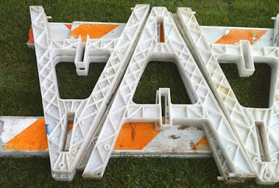Orange and white caution sawhorses lying on grass, looking like a V and an A