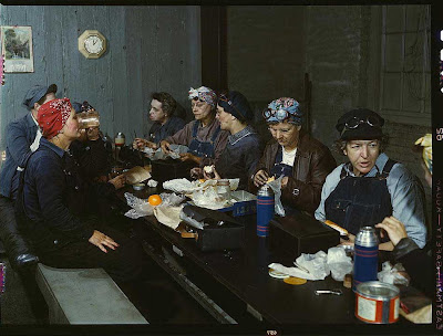 Women gathered around a long table, wearing overalls and headscarves, their lunch buckets on the table before them
