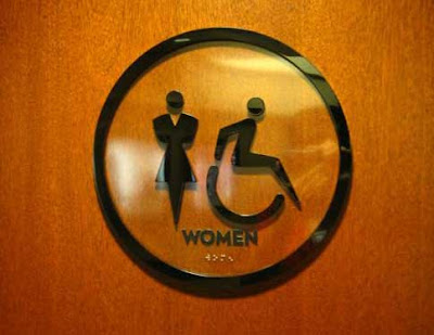 Restroom door with updated wheelchair user symbol, more active looking
