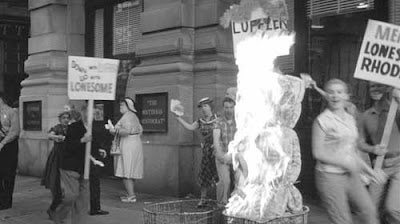 People with picket signs burning a mattress in a trash can