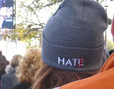 Knit cap with the word HATE embroidered on the edge. The E is crossed out with red, so it now reads HAT