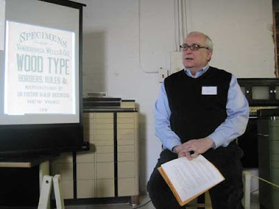Paul Gehl beside a projected screen of a wood type specimen book title page
