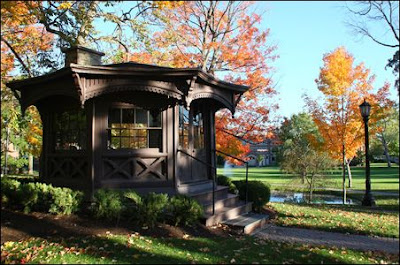 Brown Victorian gazebo on green grass with autumn leaves