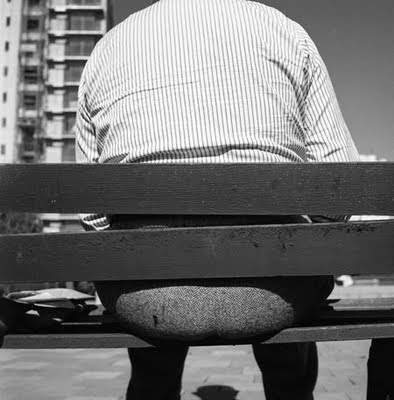 Photo of back of a park bench, showing a fat man sitting on it with his backside sticking out between the slats