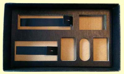 Black tray made out of layers of corrugated cardboard, each component's nest of different depth and shape