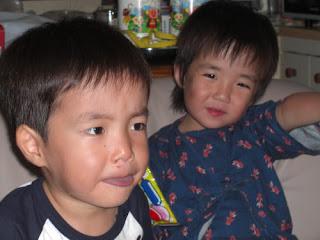 3歳の双子がソファに座っている