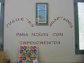 Wall in a children's classroom. Text in spanish reads: Toys adapted for children with impairments. An alphabet toy leans against the wall.