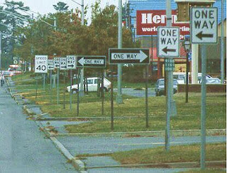 picture of one-way signs pointing in different directions along a street
