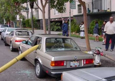 photo of a car parked in front of a hydrant with fire hose running through it