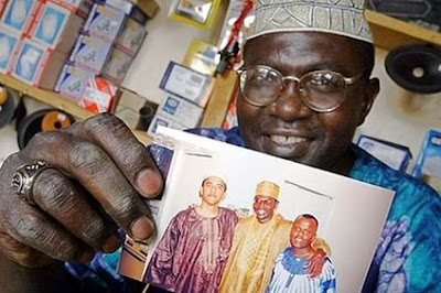 Malik Obama holds photo of brother Barack