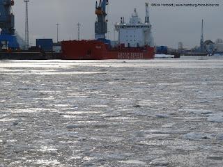 Schiff Arctic Express im Hafen von Hamburg. Winter, vereiste Elbe, Eisschollen