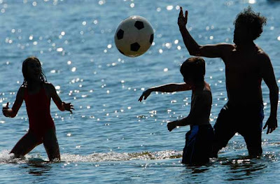 People play with a ball as they take a dip on a sunny spring day at Berlin's Wannsee lido