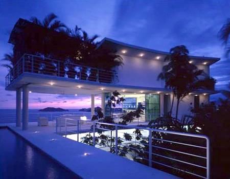 Vista nocturna de una residencia tropical contemporánea de alto estándar