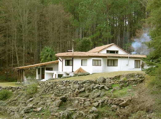 Perspectiva de la cabaña de troncos, piedras, y mampostería