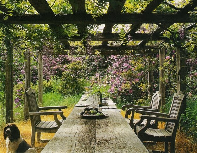 Long wooden table with wooden chairs underneath a vine covered canopy in the Vervoordt gardens, perfect for alfresco dining, Veranda Magazine Sep-Oct 2001, edited by lb for linenandlavender.net (l&l)