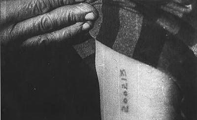 Preso de campo de concentración con el número de prisionero tatuado en el brazo