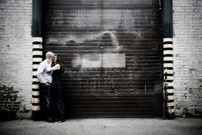 Engagement portrait of couple kissing in front of garage door in downtown Chicago alley