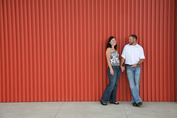 Engaged couple poses by orange wall at Harley-Davidson museum