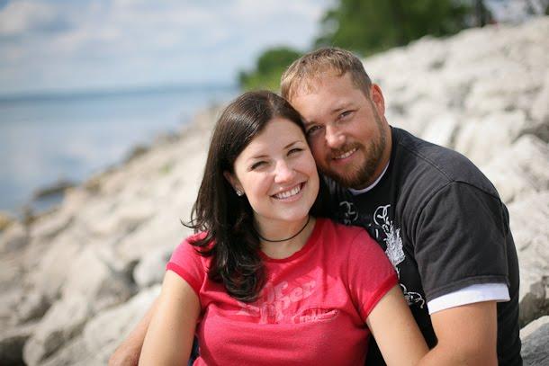Engagement portrait of couple sitting on rocks by Lake Michigan
