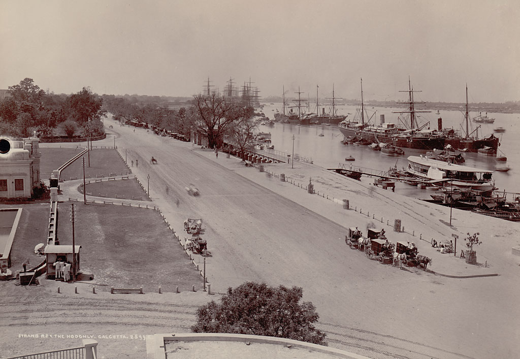 Strand Road Showing Group in Costume with Bullock Carts and Horse-Drawn Carriages, Sailing Ships and Other Boats On Hooghly River - Calcutta (Kolkata)