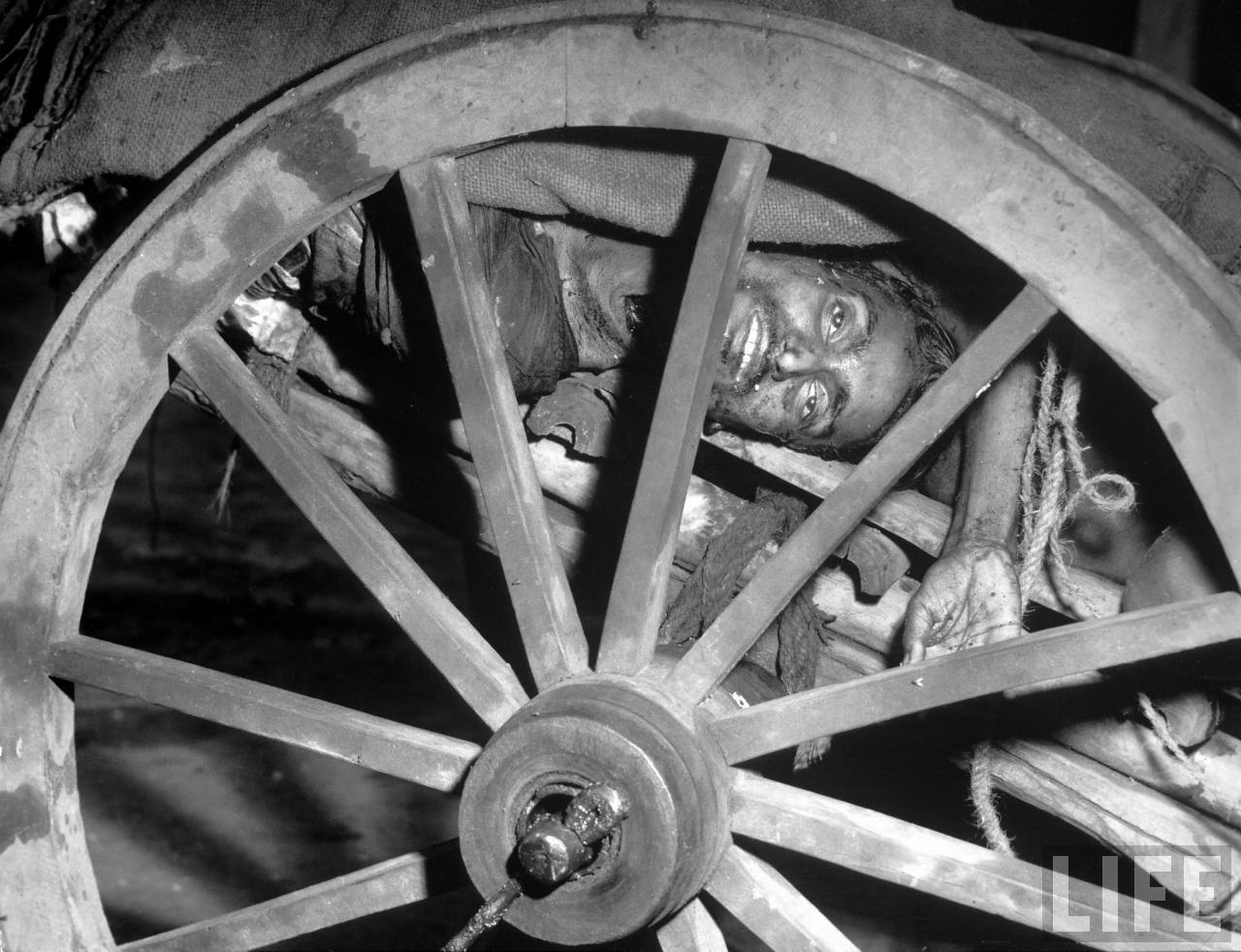 Corpse of a man seen through a wheel of a cart on its way to be cremated after bloody rioting between Hindus and Muslims