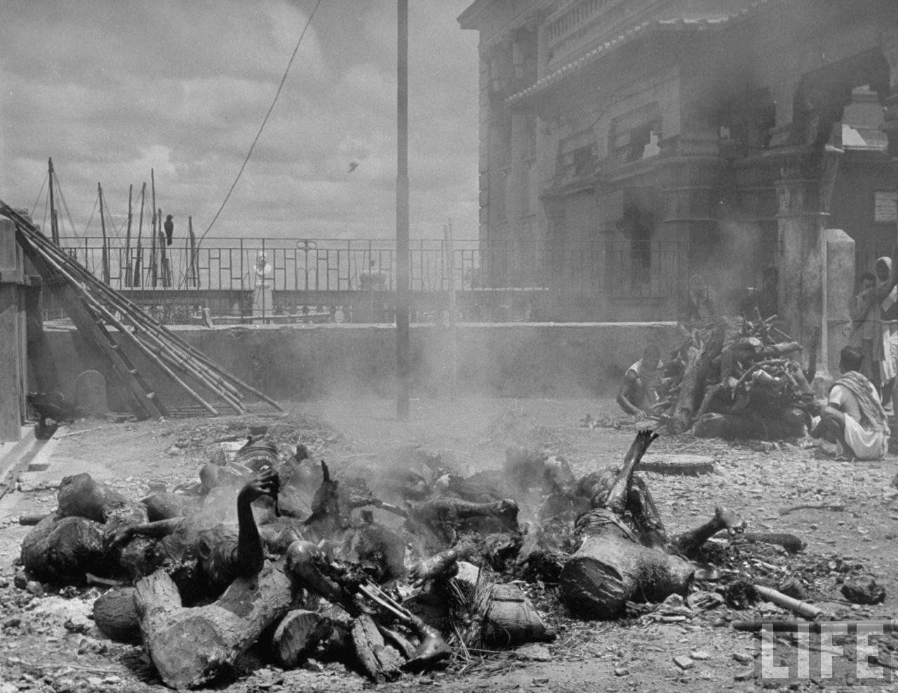 Corpses lying among pieces of wood in preparation for cremation after bloody rioting