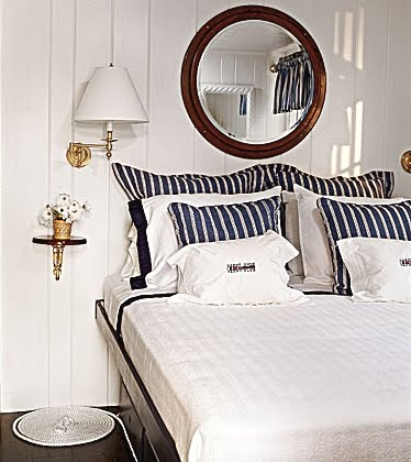 nautical bedroom idea with porthole mirror above headboard