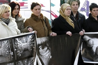 Relatives of Srebrenica victims hold photos relating to the massacre as they prepare to leave Sarajevo in Bosnia early Saturday, Feb. 24, 2007 for the Netherlands to attend Monday's verdict by the International Court of Justice in a genocide case against Serbia and Montenegro in the Hague. Bosnia-Herzegovina filed the case in 1993 — the first time a state, rather than individuals, had been charged with genocide. In case it wins, it hopes later to seek compensation for the loss of life and property during the 1992-95 war, when over 100,000 people were killed and when entire Muslim Bosniak towns and villages were devastated.