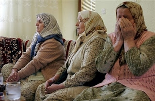 Bosnian Muslim woman Fatima Bektic, 56, right, survivors of the Srebrenica massacre, reacts during a live TV broadcast from the World Court decision in The Hague, at her in the village of Podlugovi near Sarajevo, Bosnia, Monday, Feb. 26, 2007. The United Nations' highest court on Monday exonerated Serbia of direct responsibility for the mass slaughter of Bosnian Muslims at Srebrenica during the 1992-95 Bosnia war, but ruled that it failed to prevent genocide.