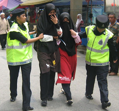 Police arresting 2 women with black tudung and veil