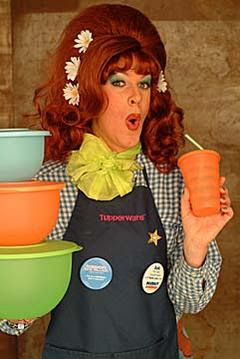woman with large red wig and Tupperware apron, holding Tupperware products
