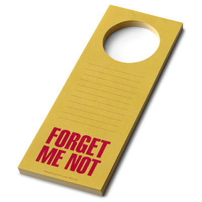 yellow door hanger pad with red writing saying Forget Me Not