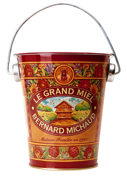 colorful pail storing honey, labeled Le Grand Miel