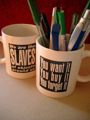 mug that says this on side 1: We are the slaves of objects around us - and this on side 2: You want it You buy it You forget it