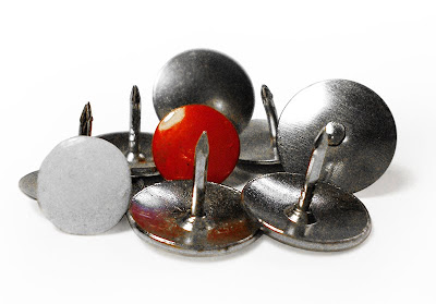 free stock photo of old-style thumbtacks, one in red and one in white, the balance silver tone, copyright J. Gracey Stinson