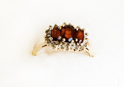 gold ring with 3 oval garnets surrounded by small diamonds