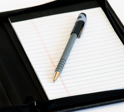 Close up of a rubber-coated ball point pen on a lined notepad