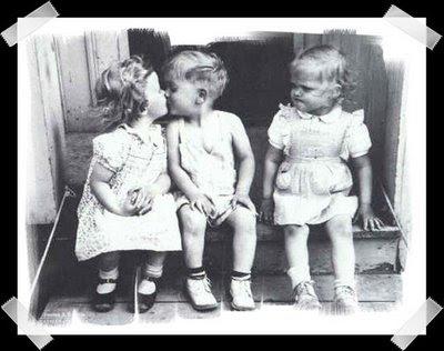 niño y niña se dan un beso y una tercera niña tiene cara de rabia