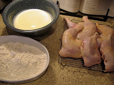 A photo of a bowl of egg mixture, a bowl of flour mixture and raw chicken resting on a wire rack.
