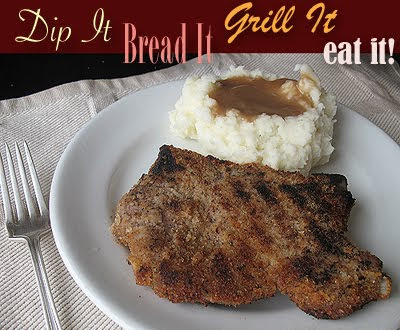 A close up photo of a grilled breaded pork chop on a white plate with mashed potatoes and gravy.