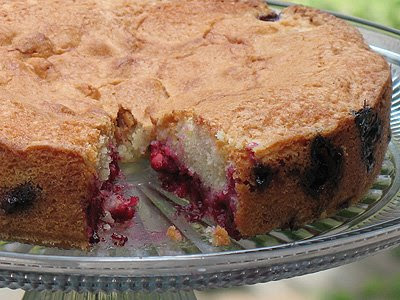 A close up photo of a cherry almond cake on a clear cake stand with slice missing .