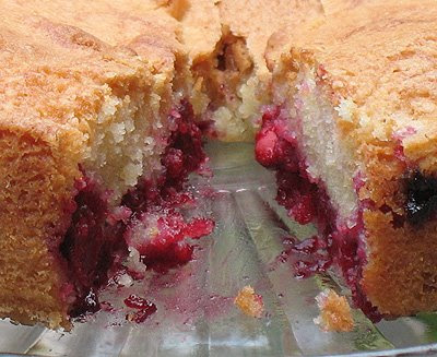 A close up photo of a cherry almond cake with a slice removed.