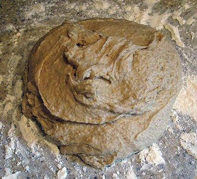 A photo of artos dough resting on a flour surface.