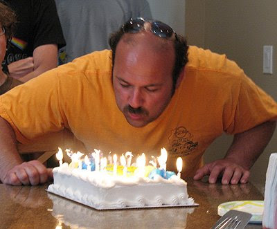 A photo of Amanda\'s friend Pete blowing out candles on a birthday cake.