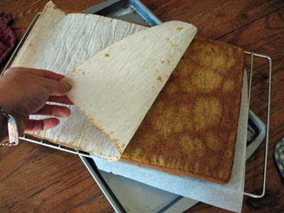 A photo of parchment paper being pulled off of a sheet of baked carrot cake.