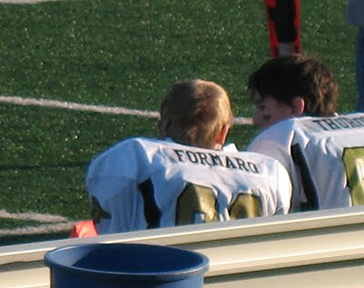 An old photo of Amanda\'s son TJ on the sidelines in his football uniform.