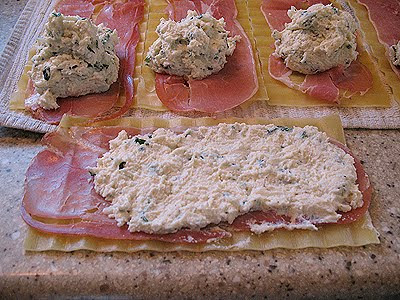 A close up photo of a dollop cheese mixture spread out on top of the prosciutto and lasagna noodles.