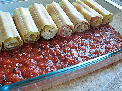 A photo of lasagna noodle rolled into a tube shape resting in a pan over sauce.